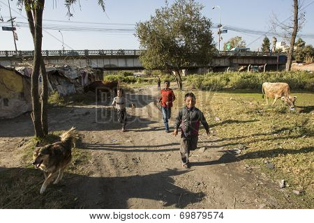 KATHMANDU, NEPAL - DEC 16, 2013: Unidentified poor children near their houses at slums in Tripureshwor district. Caste of untouchables in Nepal, is about 7 % of population.