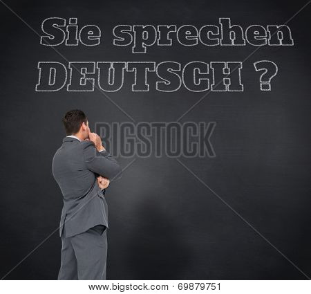 Composite image of thinking businessman against blackboard, Do you speak German?