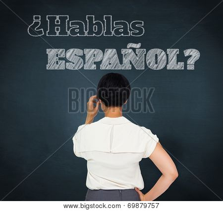 Composite image of thoughtful businesswoman against blue chalkboard, Do you speak Spanish?