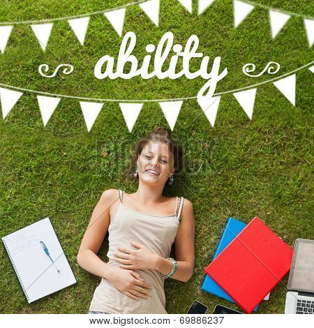 The word ability and bunting against pretty student lying on grass