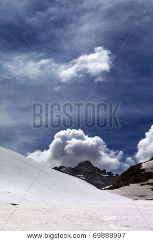 Rocks With Clouds And Snowy Plateau