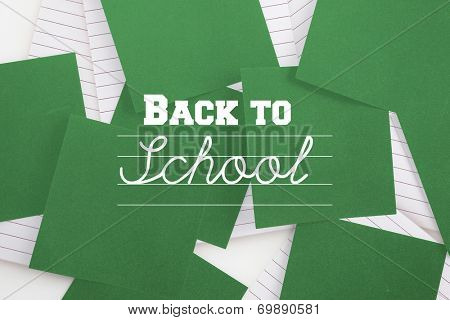 Back to school message against green paper strewn over notepad
