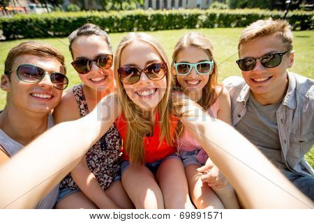 friendship, leisure, summer, technology and people concept - group of smiling friends making selfie with smartphone camera or tablet pc in park