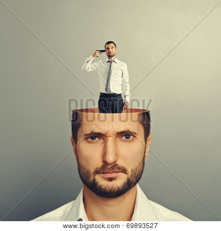 portrait of displeased man with small desperate man in his head. photo over grey background