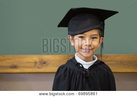 Cute pupil in graduation robe smiling at camera in classroom at the elementary school