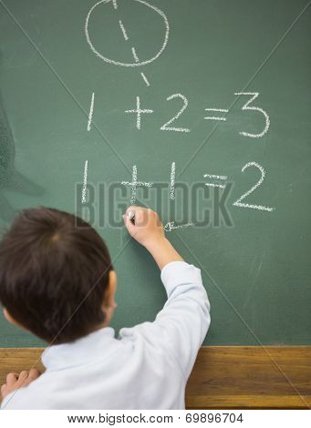 Cute pupil writing maths on chalkboard at the elementary school