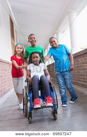 Cute disabled pupil smiling at camera in hall with her friends at the elementary school