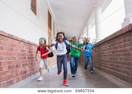 Cute pupils running and smiling at camera in hallway at the elementary school