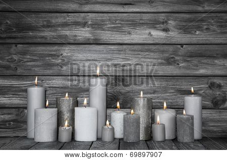 Burning Candles In White And Grey On Wooden Shabby Chic Background.