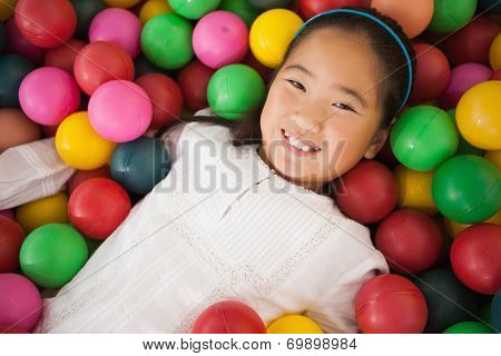 Happy girl playing in ball pool at a party