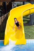 stock photo of toboggan  - Girl with glasses for swimming sliding on toboggan at aqua park - JPG