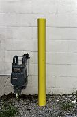 foto of utility pole  - A utility box with a yellow pole ourside the back of a building.