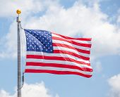 image of flag pole  - American flap flapping against a blue sky on a flag pole focus on star of waving flag
