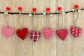 picture of pussy-willows  - Red heart shaped christmas decorations hanging on a pussy willow branch with pegs over old oak wood background - JPG