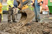 image of track-hoe  - Worker using a small tracked excavator to dig a hole to fix a water leak at a large commercial housing development in Oregon - JPG