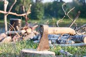picture of ax  - Ax stuck in a log on the background of the tourist camp - JPG