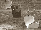 stock photo of swingset  - Sepia filter applied to retro swingset showing empty swings on playground - JPG