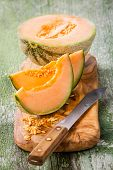picture of cantaloupe  - Cantaloupe melon slices on olive wood cutting board - JPG