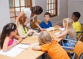 image of pupils  - Pretty teacher standing with pupils at desk at the elementary school - JPG