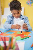 stock photo of nursery school child  - Cute little boy making art in classroom at the nursery school - JPG