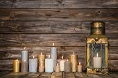 picture of burial  - Wooden vintage background in with many burning candles and a old rustic lantern - JPG