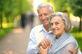 stock photo of mature adult  - Cute smiling happy mature couple posing outdoors