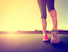 foto of jogger  -  a woman with an athletic pair of legs going for a jog or run during sunrise or sunset  - JPG