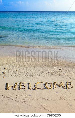 "Word "" welcome "" is written on sand on oceanside"