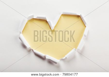 White torn paper heart over peach background