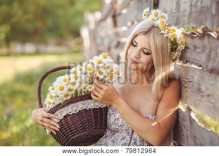 Girl with a basket of flowers in the countryside.