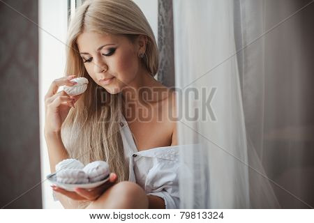 Young woman eating marshmallows, standing at the window.
