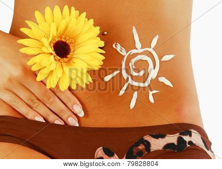 Tanned female body with yellow gerbera isolated on white background