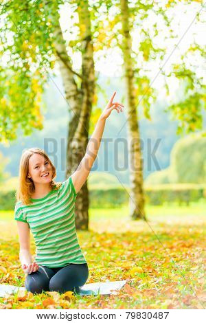 Girl With A Beautiful Smile Sitting In The Park And Shows The Upstairs