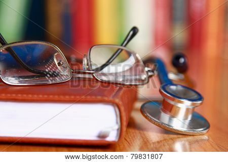 Close-up of a notebook, spectacles, stethoscope on the desk