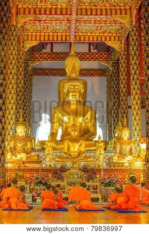 CHIANG MAI, THAILAND - NOVEMBER 18, 2014: Young buddhist monks praying in front of the Buddha image in Wat Suan Dok temple in Chiang Mai, Thailand on 18 November, 2014