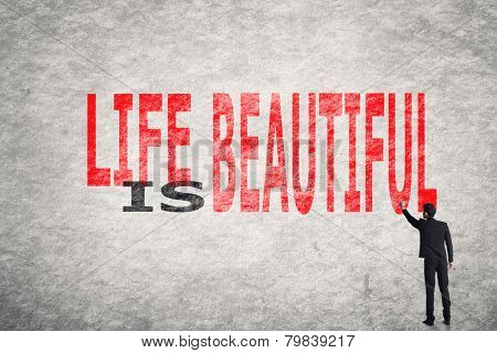 Asian businessman write text on wall, Life is Beautiful