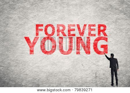 Asian businessman write text on wall, Forever Young
