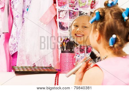 Small smiling girl with hair-curlers, face brush