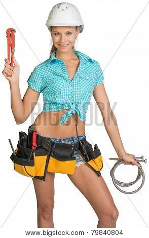 Pretty girl in helmet, shorts, shirt, tool belt with tools holding flexible hose and wrench