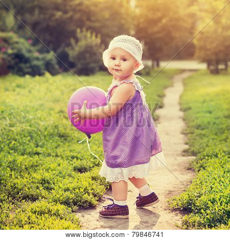 Little girl with a purple balloon