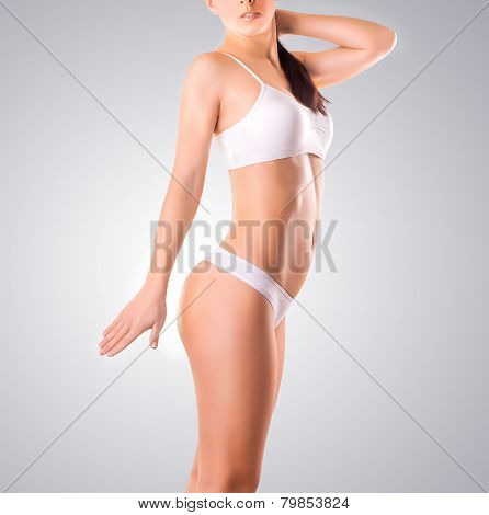 Slim tanned woman's body isolated over gray