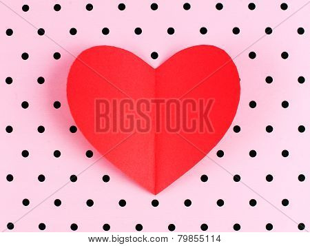 Paper heart on polka dot background