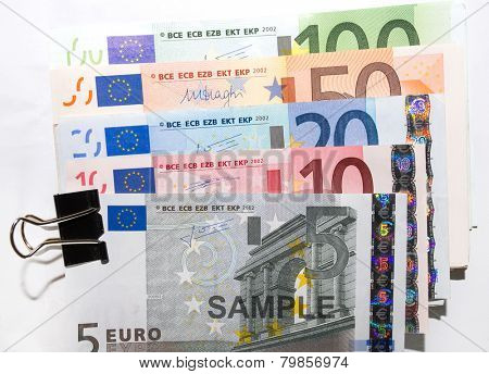 Various denominations of EURO currency banknotes held in a clip