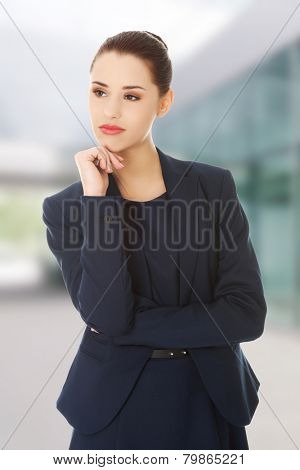 Thinking businesswoman standing and contemplating.