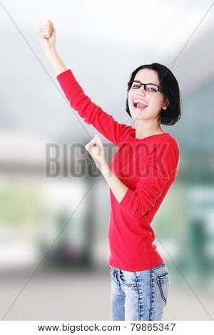 Excited young woman with fists up