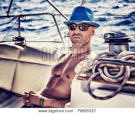 Sexy sailor, man on sailboat enjoying cruise, vintage style photo of a handsome shirtless model sailing on a luxury water transport, fashion lifestyle concept