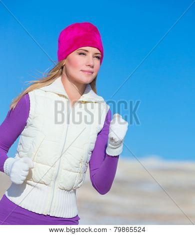 Jogging outdoors, portrait of cute sportswoman running outside, workout in winter time, sportive achievement, active lifestyle concept