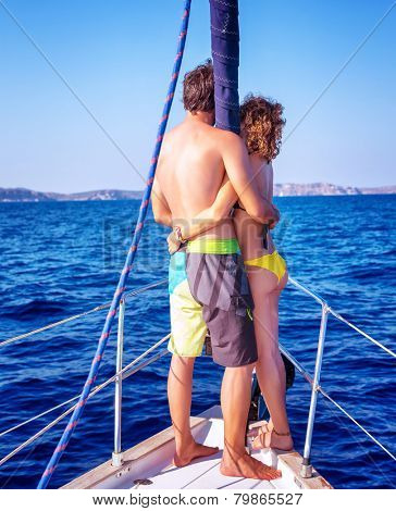 Back side of happy young couple standing on the deck of luxury sail boat, romantic date in sunny summer day, enjoying each other concept