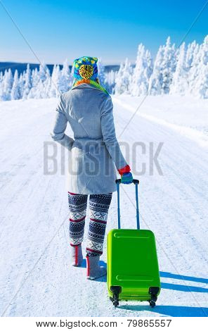 Traveling to Alps, back side of a young woman walking along snowy road with stylish green luggage,  winter vacation in Europe