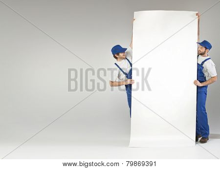 Two employees holding white banner